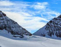 蓝天白云下的积雪与山峰摄影图片