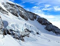 蓝天白云下的美丽雪域山峰摄影图片