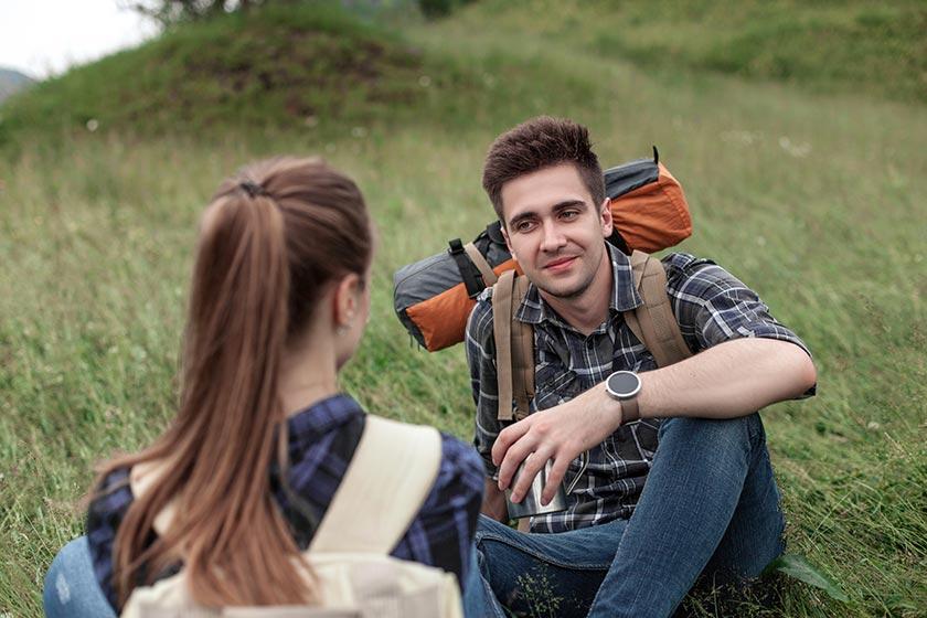 坐在草地上聊天的青年男女摄影图片