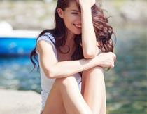 坐在岸边微笑的性感美女摄影图片