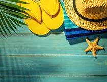 木板上的拖鞋草帽毛巾海星摄影图片