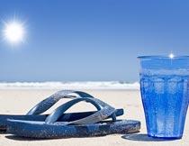 沙滩上蓝色人字拖鞋与水杯摄影图片