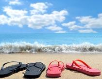 沙滩上的人字拖鞋与海浪摄影图片