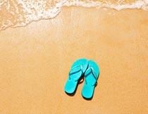 沙滩上的潮水与蓝色人字拖摄影图片