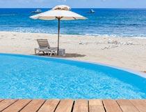 海边泳池与沙滩遮阳伞躺椅摄影图片