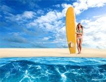 沙滩上比基尼美女与冲浪板摄影图片