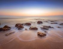海岸边唯美的沙滩岩石美景摄影图片