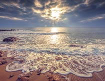 夕阳下海浪冲打着沙滩美景摄影图片