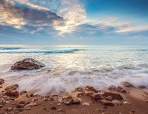 美丽晚霞下海浪冲打着岩石摄影图片