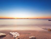 美丽黄昏下的大海沙滩岩石摄影图片