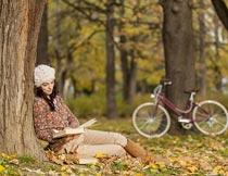 秋天靠在大树上看书的美女摄影图片