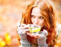双手捧着杯子喝茶的美女摄影图片