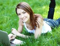 趴在草地上开心上网的美女摄影图片