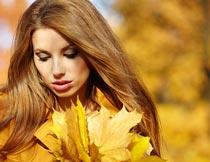 低头拿着落叶的美女模特摄影图片