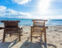 阳光下沙滩上的休闲躺椅摄影图片