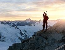 黄昏登上雪域山峰的男人摄影图片