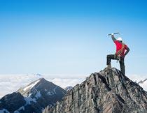 蓝天下山顶欢呼的登山者摄影图片