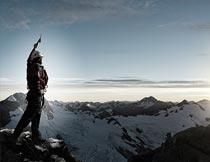 雪域山顶上举手欢呼的男人摄影图片
