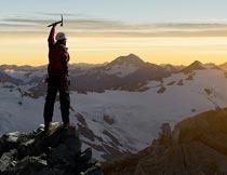 黄昏登山雪域山峰的男人摄影图片