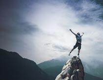 山顶上张开双臂的男人特写摄影图片