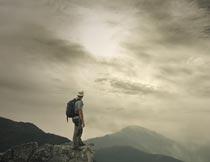 悬崖上欣赏云端风光的男人摄影图片