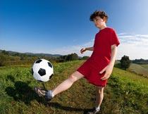 郊外草地上踢足球的小男孩摄影图片