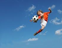 高空中踢足球的小男孩特写摄影图片