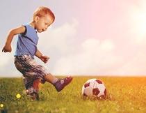 阳光下草地上踢足球的男孩摄影图片