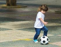 公园路面上踢足球的小女孩摄影图片