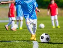 一起踢足球的儿童局部特写摄影图片