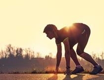 黄昏道路上准备起跑的男人摄影图片