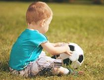 坐草地上玩足球的小男孩摄影图片