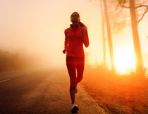 日出马路上晨跑的美女特写摄影图片