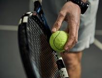 手拿网球拍和网球的男人摄影图片