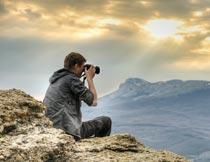 日出坐在高山上拍照的男人摄影图片