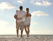 站沙滩上拥抱的一家人背影摄影图片