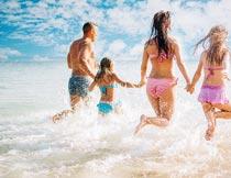 海水里奔跑的四口之家背影摄影图片