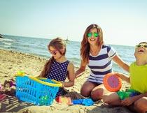 坐沙滩上陪孩子玩沙的妈妈摄影图片