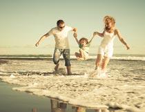 海边开心玩耍的三口之家摄影图片