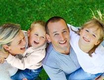草地上抬头的幸福四口之家摄影图片