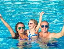水中竖起大拇指的三口之家摄影图片