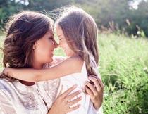 草丛边幸福拥抱对视的母女摄影图片