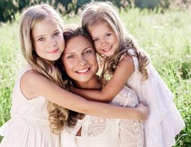 草丛边拥抱着妈妈的俩姐妹摄影图片