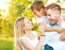公园开心背着孩子的一家人摄影图片