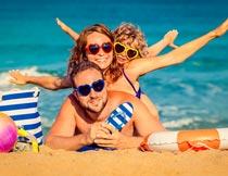 海边沙滩上戴墨镜的一家人摄影图片
