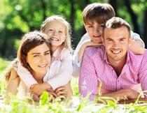背着孩子趴在草地上的父母摄影图片