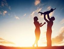 夕阳下高兴孩子的夫妻剪影摄影图片