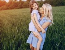 黄昏稻田里抱着女儿的母亲摄影图片