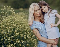 黄色小花边抱着女儿的妈妈摄影图片