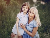 草丛中蹲着抱着女儿的妈妈摄影图片